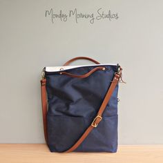 Ooh! Love. In navy. Convertible tote bag that can be used as a messenger bag, shoulder bag, foldover purse, or tote. Made of high quality waxed 10.10 oz Army