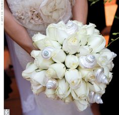 Margo opted for a classic, round, all-white rose bouquet. The twist: A conch shell took the place of a bouquet wrap, and iridescent shells were mixed in with the blooms!
