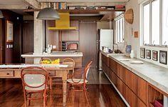 O arquiteto Gustavo Calazans integrou a cozinha à área social. Ele criou uma estrutura de madeira no teto que tem duas funções: iluminação, sobre a bancada, e prateleira para livros, na parte virada para a sala