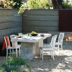Before: Salvaged Pavement, After: Outdoor Tabletop -  This outdoor dining table was given an industrial upgrade with a tabletop made of solid concrete, salvaged from a garden remodel. The table required two car jacks in order to be built, but recycling the concrete was an inexpensive makeover.