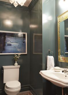 Bohemian Traditional Bathroom: Large scale framed art hanging above toilet in green walled bathroom..
