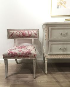A fresh take on the classic klismos style, the Aria Side Chair features a hand applied white wash finish, hand carved frame, sabre legs, and white upholstery. Custom upholstery is available. It is shown here with the Swedish Gustavian inspired two-drawer dresser which features elegant hand carvings with laurel wreaths at the center of each drawer. The dresser is hand finished in an ethereal blue with light distressing.   Aria Collection from Ave Home