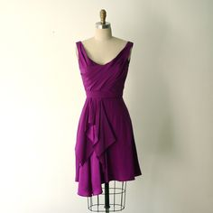 Electric violet crepe de chine and charmeuse draped scoop neck dress with ballet back, self belt, and flowy skirt.  Hem hits a couple inches above the knee.  Invisible zipper at center back.Handmade in the heart of NYC's fashion district. For single orders please allow up to 10 weeks for production if not in stock. Return/exchange within 10 days of receipt.Please email dara@carol-hannah.com for info on colors, lead times, multiples for bridesmaids. Available long for $625.