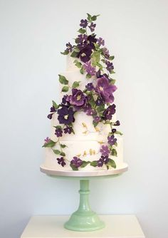 Ultra violet flowers adorn this beautiful cake which also has small gold bird details. #UltraViolet #WeddingCake