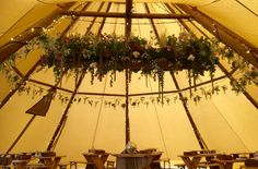 Tipi decorated with a floral 'scaffolding' board swing, hanging bottles, for a woodland wedding.  Flowers by Spriggs Florist