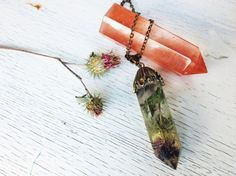 A piece of nature enclosed in a crystal. Pendant is made using a dried flower in clear resin. The length of the chain is 48-53cm. Crystal is about
