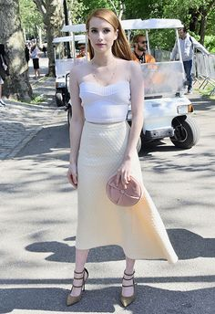 Shake up your wedding guest wardrobe with a knitted bandeau top and high-waisted midi combo, à la Emma Roberts. Pastel palettes, pointed heels and a pillow clutch = your secrets to fancy chic