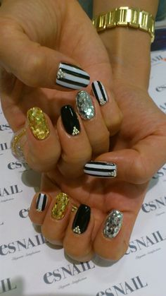 black and gold striped sparkly nail design