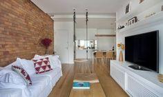 Móveis e marcenaria branca dão um ar bem clean à sala, que tem uma das paredes revestidas de tijolinhos