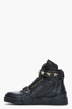 GIVENCHY //  Black Leather Star-Embellished High-Top Sneakers  31278M050012  High top leather sneakers in black. Round toe. Black lace up closure with gold tone eyelets. Foldover velcro strap at ankle with faceted metal star embellishments in gold tone. Paneled upper with embossed logo at side. Ribbed panel at heel. Textured black rubber foxing. Tone on tone stitching. Leather upper, rubber sole. Made in Italy.  $775 CAD