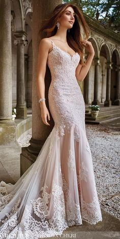 Sleeveless re-embroidered Alençon lace on tulle over soft satin sheath with hand-beaded spaghetti straps, softly curved scalloped V-neckline with illusion modesty panel, dropped waist lace bodice, elongated sheer lace overskirt with scalloped hem spills into chapel length train.