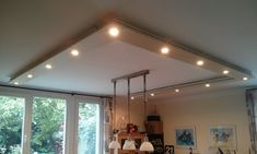 I wanted to create an attractive living room lighting around the lamp over the dining table. I've used KVARTAL curtain rods (and accessories) to hang IKEA HAGANÄS drawer panels