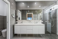 The grey floor to ceiling tiles in this bathroom make the space appear even bigger! Plus, it emphasises the heavy veining in the calacutta splashback. Try a monochromatic colour scheme in your bathroom. Monochromatic Color Scheme, Grey Flooring, Splashback, Ceiling Tiles, Cabinet Design, Cabinets, Custom Design, New Homes, Interiors
