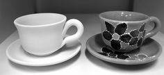 gray cup and saucer with a black flower