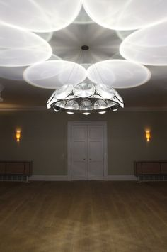 Chandelier with 12 lenses,  Rosegold-plated aluminium, glass, fresnel lens, custom electronics.  Seems as though you would get a nice, diffuse light in the room.