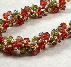 9 inches (23 cm) of twisted red and olive Swarovski crystals and gold glass seed beads.  Designed by Val on etsy