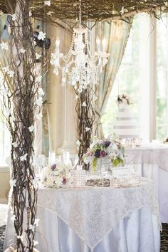 The couple's sweetheart table was draped with a floral-embroidered overlay and topped with an arrangement of ivory and lavender flowers. A stunning pergola made of branches and adorned with white blooms covered the table and suspended an elegant crystal #chandelier. Photography: Images by Berit, Inc.