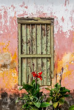 A Spanish window in the old colonial town of Remedios with peeling paint on the wall.