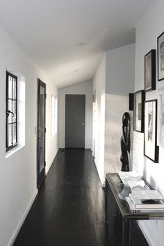 I want a black floor! Sneak Peek, Best of: Black & White - The hallway in Jeff Gnewikow and Jeff Madalena's Catskills home features bright white walls complemented by a stunning floor, painted black with India ink. Style At Home, Sol Sombre, Black Wood Floors, Black Floorboards, Le Living, Living Room, Hallway Flooring, Dark Flooring, Wooden Flooring