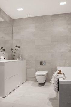 Proste formy szafki i wanny w połączeniu z szarymi kaflami na podłodze i ścianach tworzą ascetyczny, harmonijny wystrój tej łazienki. Srebrne pojemniki są jej jedyną ozdobą. Efektywne oświetlenie we wnętrzu zapewniają oprawy wpuszczane w sufit.