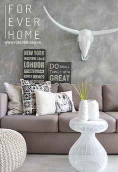 Modern living stoer interieur, grijstinten, bull, betonlook muur, sierkussens, gebreide poef, naamborden