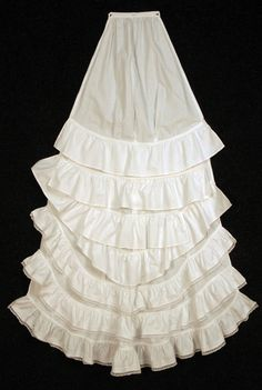 Rare trained evening petticoat, c. 1878. White cotton intended to button onto back of an under-petticoat for more formal occasions, having six self ruffles, the lower three with tucks and lace edging. Courtesy of Charles A. Whitaker Auctions.