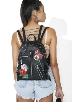Current Mood Love Me Not Backpack there's not even a question, babe, everyone luvs yew! No need to pluck petals off da flowerz when yew got this backpack that features a black vegan leather construction, double shoulder straps on each side, a top zipper closure, silver zipper N' stud details, and bloomin' embroidered flowers on da front.
