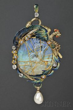 This one is from Skinner Auction. Look closely at the carved opal inside the gold, enamel, pearl and diamond setting… Does it remind you of anything? See Jewelry Nerd for answers