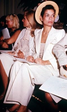 Bianca Jagger sitting front row in a white suit, 1971