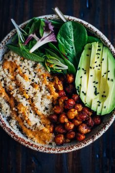 This vegan buddha bowl has it all - fluffy quinoa, crispy spiced chickpeas, and mixed greens, topped with a mouthwatering red pepper sauce! #vegan #healthy