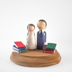 A bookish wedding topper that you can customize to look like you and your partner.
