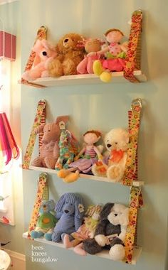 What a cute fabric and wood shelf for stuffed animals or dolls. It kind of looks like the toys are sitting on a swing. Would be easy to make and you could pick your fabric to match the curtains, walls and bed linens..