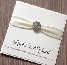 The elegant handmade Luxury classic wedding invitations from Chosen Touches of Halifax uses double sided satin ribbon and a beautiful diamante brooch.