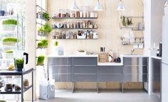 Kuchyně s nerezovými díly IKEA, dřevem obloženou zdí, bílými doplňky a množstvím zeleně.
