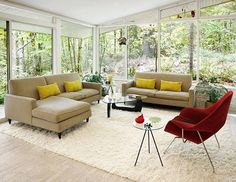 Modern living room with floor to ceiling windows, two taupe sofas with yellow accent pillows, a Noguchi glass coffee table and a red Eero Sa...