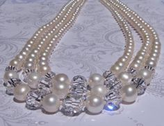 Absolutely fabulous vintage design reproduction! Three strands of gorgeous, luxurious and lustrous cream color real Freshwater Pearls in graduated sizes with an incredible center of Genuine Swarovski Crystal Clear Round Crystals. The smallest crystal is 10mm and the largest crystal is