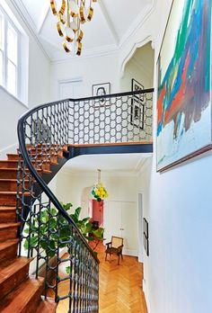 A glamorous hallway full of colour and texture. The unusual iron balustrade, striking gold light, parquet flooring and colourful artwork all add interest to this large hallway.