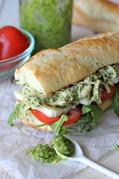 chicken pesto sandwich ~ 2 cups shredded chicken breast ~  1/2 cup basil pesto, or more to taste ~  1/4 cup greek yogurt ~  salt & pepper, to taste ~  1 toasted baguette, cut into 3-4 equal pieces ~   arugula ~  sliced tomatoes ~  4 ounces mozzarella, thickly sliced