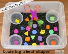 Learning about shapes in a sensory bin activity. You will need a small tub, 4 small containers, handy scoopers, shape buttons, and black aquarium rocks. The black aquarium rocks really bring out the colors in the shape buttons. Motor Activities, Sensory Activities, Classroom Activities, Preschool Activities, Activities For Children, Preschool Shapes, Therapy Activities, Sensory Tubs, Sensory Boxes