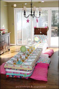 Tell kids to bring their own pillows to sit on while eating (eliminates lack of chair issue!)  Not sure where I would find a low table like this though. maybe cardboard boxes as tables covered in tablecloths.