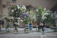 Wedding flowers grown by Mother-of-the-Groom. Rustic and country selection. Beautiful blues, whites and purples. We collected the jars and decorated them with blue and white electrical tape and raffia.