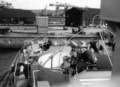 """NH 103336. USS Sausalito (PF-4). View looking forward from the ship's port bridge wing, circa 1952. Probably taken at Yokosuka, Japan Photographed by James Edward Taylor, who was then a member of Sausalito's crew. Note the ship's # 2 3""""/50 gun mount, with a training limit framework around it to prevent firing into the ship's own structure. A floater net bin is in the lower left. Collection of James Edward Taylor. Courtesy of his wife, Mary A. Taylor, 2005. U.S. Naval History and Heritage..."""