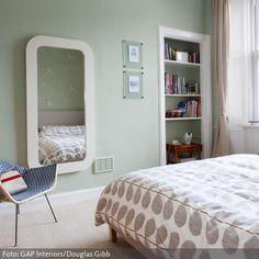 Die Raumgestaltung mit Pastellfarben hat eine beruhigende Wirkung, die für Schlafzimmer oft erwünscht ist. Eintönig muss sie deswegen nicht sein:  Hellgrün ist beispielsweise eine Wandfarbe, die oft unterschätzt wird. Sie wirkt frisch und trotzdem sehr sanft. Grau und Beige harmonieren mit Hellgrün, wie an der gemusterten Bettwäsche deutlich wird.