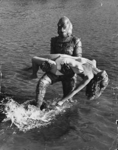 """Actress Julia Adams is carried by monster """"gill man"""" in the movie """"Creature from the Black Lagoon,"""" 1954."""
