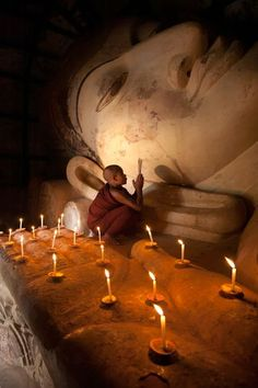 A Buddhist monk prays by candlelight in a temple in the ancient city of Bagan, Myanmar (Burma). Photo credit Kyle Hammons