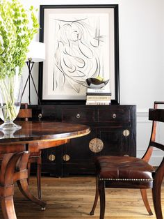 Leather klimos embellished with nail head trim paired with round dining table and ebonized Asian inspired sideboard with abstract art.