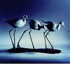 """This graceful trio of avocets with their slender upturned bills make a stunning decorative piece. Like many of his artworks, this piece also features the close dependence of the birds on the group. This 12"""" high and 22"""" wide piece of art will benefit from the natural light of a window setting to bring out its delicate patina. An edition of nine."""