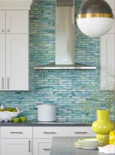 White cabinets with beautiful beach inspired tiles in sea color More
