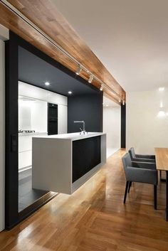 The apartment is visually divided by the oak parquet that spans the wall and ceiling. It gives an open view from the foyer to the living room making the apartment seem larger · Love Project Apartment