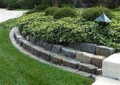 Layers of cobble edging showcase a planting bed while acting as a ...